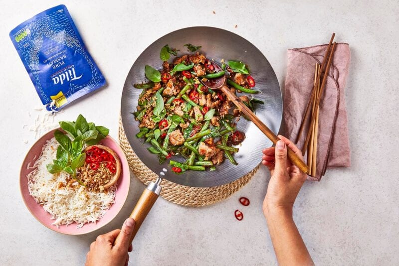 Thai Basil Pork Stir Fry in a wok with ready-to-eat rice