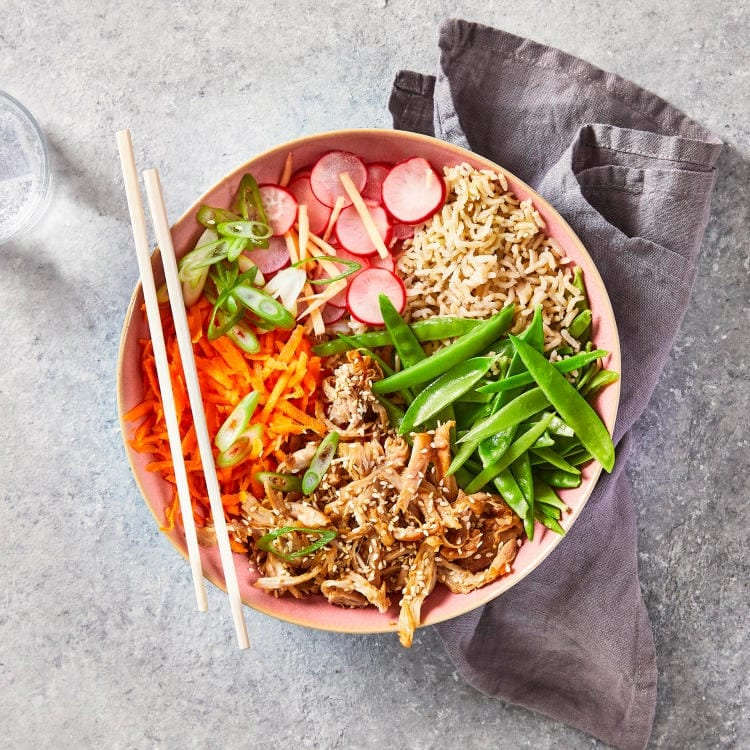 A bowl of rice topped with teriyaki chicken, grated fresh carrot, sugar snaps and picked radish on top, with chopsticks resting on the side of the bowl.