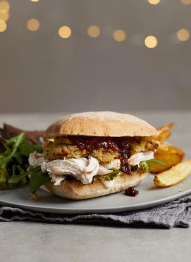 A ciabatta sandwich with pulled chicken, stuffing and plum chutney with wedges and salad.