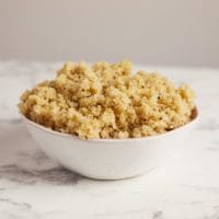 Bowl of cooked, fluffy white quinoa on marble surface