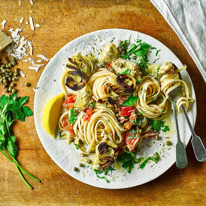 Linguine with artichokes and lemon wedge